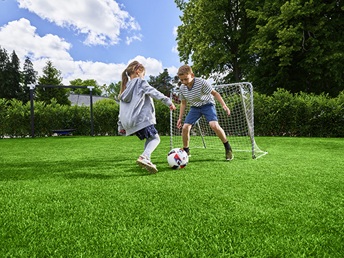 Kids playing with a football on grass. Link to the webpage roots under lawns